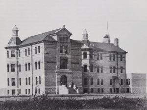 This is a black and white photo of the Selkirk Mental Hospital in 1887. It is a tall building with multiple floors and windows. There are men sitting on the front steps. The building is surrounded by empty fields.