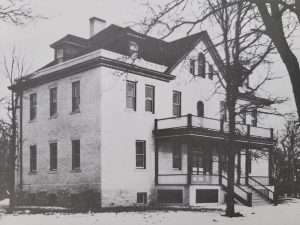 This is a black and white photo of the Selkirk Hospital in 1908. It is a tall building with windows and a balcony above the front porch and entrance.