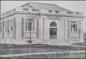 """This is a black and white photo of the Carnegie Library on Eaton Ave, taken in 1913. It is a big brick building with large windows and """"Public Library"""" written across the top."""