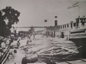 This is a black and white photo of a large ship unloading lumber at the Selkirk docks in 1910. There are men unloading the lumber off the boat into piles on the dock.