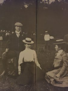 This is a black and white photo from 1898 of a man and woman sitting on the ground having a picnic with another woman at Selkirk. The women are both wearing long skirts and hats. The man is wearing a black coat with a white button up shirt, tie and hat.