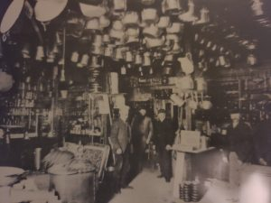 This is a black and white photo taken in 1903 of the Moody Hardware store interior. There are four men inside the store with what looks to be empty paint cans hanging from the ceiling. The inside of the store is crowded with various objects.