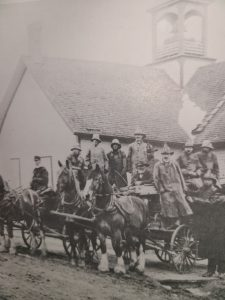 This is a black and white photo taken in 1905 of the Selkirk Volunteer Fire Brigade. There is a group of men on horse carriages with three horses in front. They are all wearing long firefighter jackets and hats.