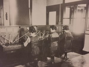 This is a black and white photo from 1927 of the telephone operators at the Selkirk Exchange Circa. There a three women sitting together at desks with headsets on.