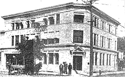 This is a black and white photo of the Dominion Bank in 1913. There are three men standing in front of the building on the sidewalk, and carriage with horses waiting down the street underneath a tree.