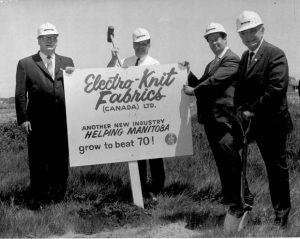 """This is a black and white photo of four men hammering a sign that says """" Electro-Knit Fabrics (Canada) LTD."""" into the ground. they are wearing suits with button up shirts and ties."""