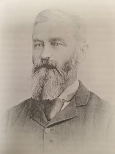 This is a black and white photo of Frederick William Colcleugh, he has a long bushy beard and moustache. He is wearing a collared jacket with a white button up shirt and a tie.
