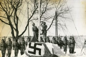 This is a black and white photo taken in 1942 of German Soldiers raising the Nazi flag on a tall post. There are two men raising the flag, with two rows of men standing at attention with their guns