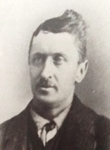This is a photo of J. Colcleugh in a black dress coat wearing a white button up shirt and a tie. He has groomed hair and a small moustache.