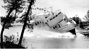 This is a black and white photo of the Lord Selkirk II launching in the river. There is a big white boat making a big spray and is strats out in the water.