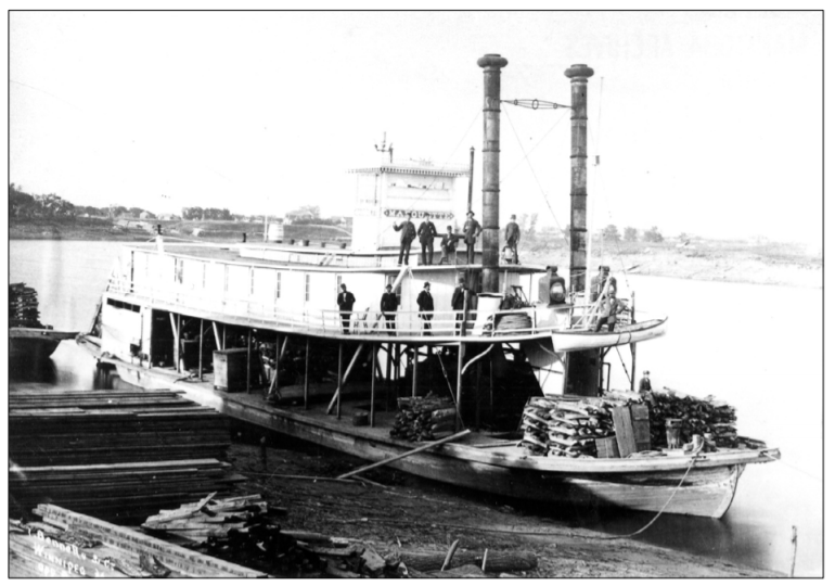 This is a black in white photo of a large steam boat in 1884. There is different cargo on board, along with a handful of crew members.