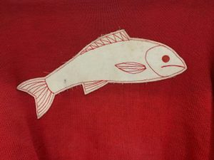 This is a photo of a white felt patch in the shape of a fish sewn onto a red piece of fabric. The detailing is sewn onto the fish with red string.
