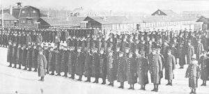 This is a black and white photo taken in 1916 of the 108th Battalion at the Red Feather Farm. There are multiple rows of men standing at attention in long black button up coats with hats.