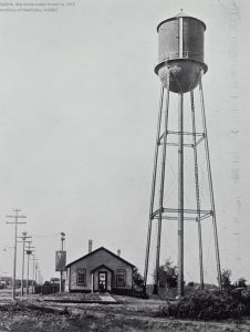 This is a black and white photo of the selkirk water tower taken in 1913. The water tower is very tall and is beside a small building.
