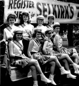 """This is a black and white photo of a group of women from Selkirk's 75 Anniversary. The women are wearing skirts and a white top with a hat and a sash that says """"Selkirk 75 Anniversary""""."""