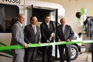 "This is a photo of CAO Duane Nicole cutting a green ribbon with ""Selkirk Transit"" spelled across the front. Duane Nicole is alongside local NDP leader Greg Dewar, and Mayor Larry Johannson. They are all dressed nicely in suits, in front of a city of selkirk transit bus."