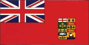 This is a photo of the Canadian Red Ensign. It is a red flag with the British flag in the top left corner, and the shield of the coat of arms of Canada towards the bottom right.