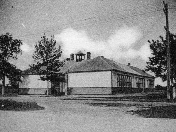 This is a black and white photo of South Ward School. It has windows along the side of the building with trees along the outside.
