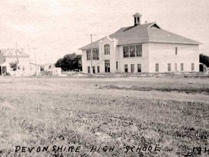 This is a black and white photo of Devonshire School in 1919. it is a tall two story building with windows along each floor. in front of it is an empty field, and there are buildings to its left.