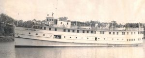 This is a black and white photo of the Keenora ship. There are lots of passengers on the top deck of the boat while the boat is sailing down the river.