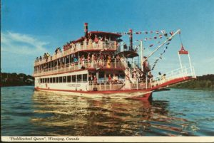 This is a photo of the Paddlewheel Queen going down the river filled with passengers. The boat is white and red and has three levels.