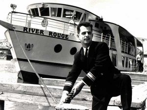 This is a black and white photo of Captain Ritchie tying up the River Rouge ship in 1967. He is wearing a black suit with a white button up shirt and a tie. He has dark hair and a groomed moustache.