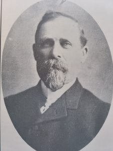 This is a black and white photo of CPT William Robinson. He has a small bushy beard and moustache and is wearing a black coat with a white button up shirt and tie.