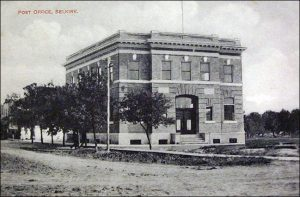 This is a black and white photo of the Selkirk Post Office taken in 1909. It is a tall building with many windows and front entrance. There are trees along the side of the building on the corner or the road.