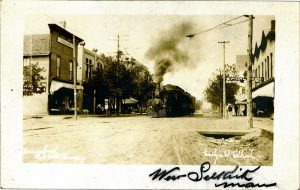 This is a black and white photo of The Selkirk Railway in 1906. There is a big black train with black smoke coming out the front going down the tracks with buildings on either side.