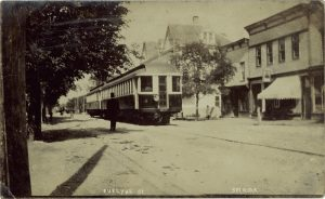 This is a black and white photo of the electric railway running through Selkirk in 1909. There are buildings on one side of the train, and a man waiting and watching the train on the other side.