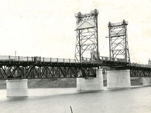 This is a black and white photo taken in 1936 of the Selkirk Lift Bridge. The steel bridge goes over top of the Red River. The center of the bridge has two high towers that have a pulley system to lift the middle of the bridge to allow ships to pass through.