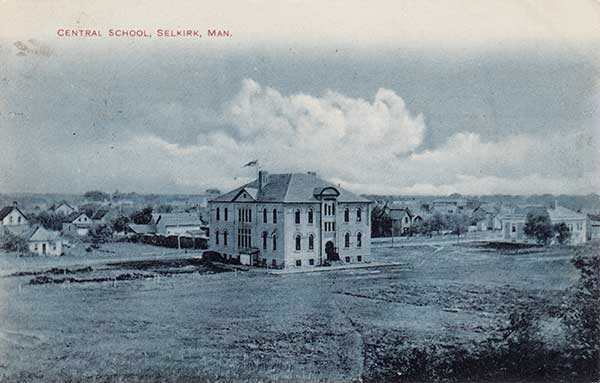This is a black and white photo of Selkirk Central School in 1907. It is a large and tall building with multiple windows, surrounded by field space. There are many house across the street in the background.
