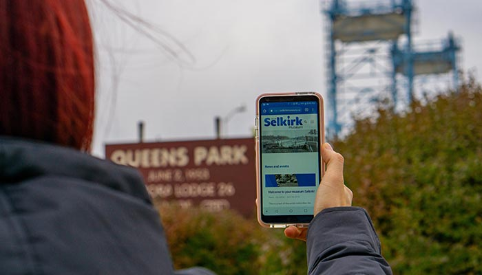 This is a photo of someone holding up their phone, with the selkirk website on their screen.